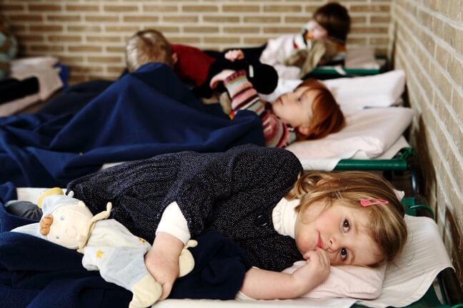 Kleuters liggen op bedjes in de slaapklas