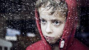 Jongen kijkt droevig door het raam