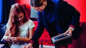 De leraar geeft uitleg aan een leerling die werkt met een tablet in de klas