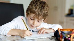 Jongen maakt huiswerk aan tafel