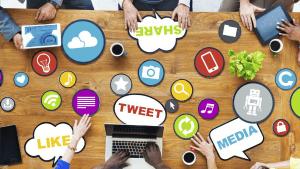 Handen rond een tafel die tokkelen op laptops en tablets om social media te gebruiken.