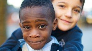Zwart en blank kind in omhelzing