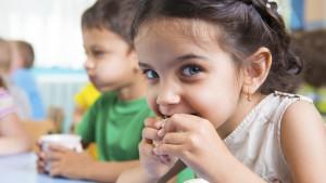 Meisje eet in schoolrefter