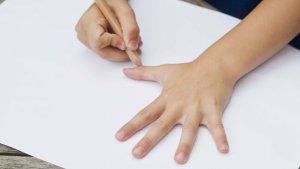 leerling tekent hand op blad papier