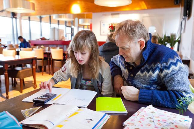 Ouderparticipatie: Vader begeleid dochter met huiswerk in de huiswerkklas