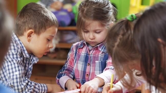 drie kinderen in een kleuterklas