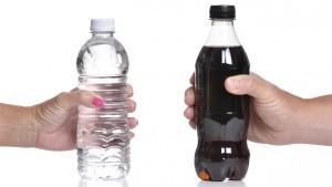 handen die een flesje water en een flesje cola vasthouden