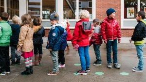 Leerlingen lagere school staan in de rij op groene stippen