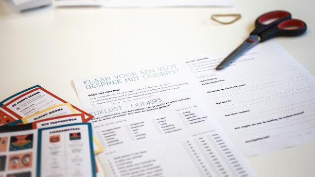 checklists en praatkaartjes liggen op een tafel
