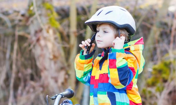 jongen zit op zijn fiets en gespt helm vast