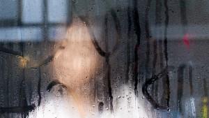 Meisje achter aangedampt raam