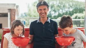 2 kinderen spuwen tandpasta in kommen die vastgehouden worden door man