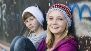 Meisje en jongen zitten tegen muur