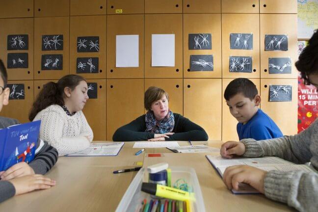 Juf begeleidt groepje leerlingen tijdens een taalles.