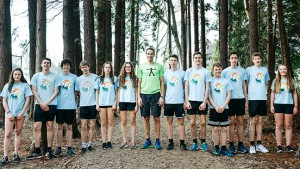 Leraar en leerlingen staan in sporttenue naast elkaar in een bos