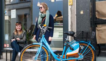 Meisje met blue-bike in stad aan etalage