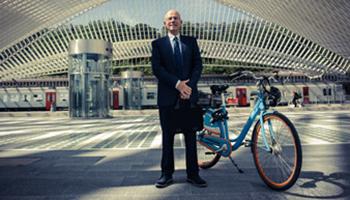 Zakenman met aktetas staat op plein met blue-bike fiets langs hem
