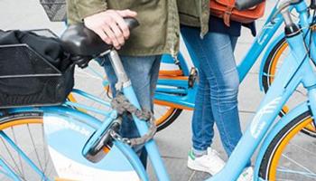 2 personen wandelen buiten met blue-bike fiets aan de hand