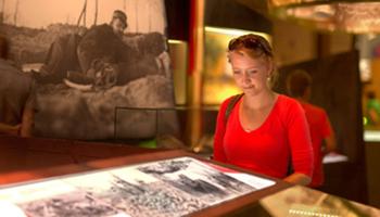 Vrouw kijkt naar foto's uit WOI (In Flanders Flieds Museum)