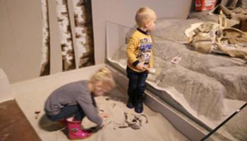 Kinderen graven botten op in het zand