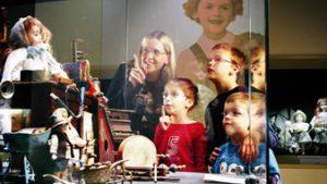 Mama met kinderen kijken naar vitrine met oude poppen en speelgoed