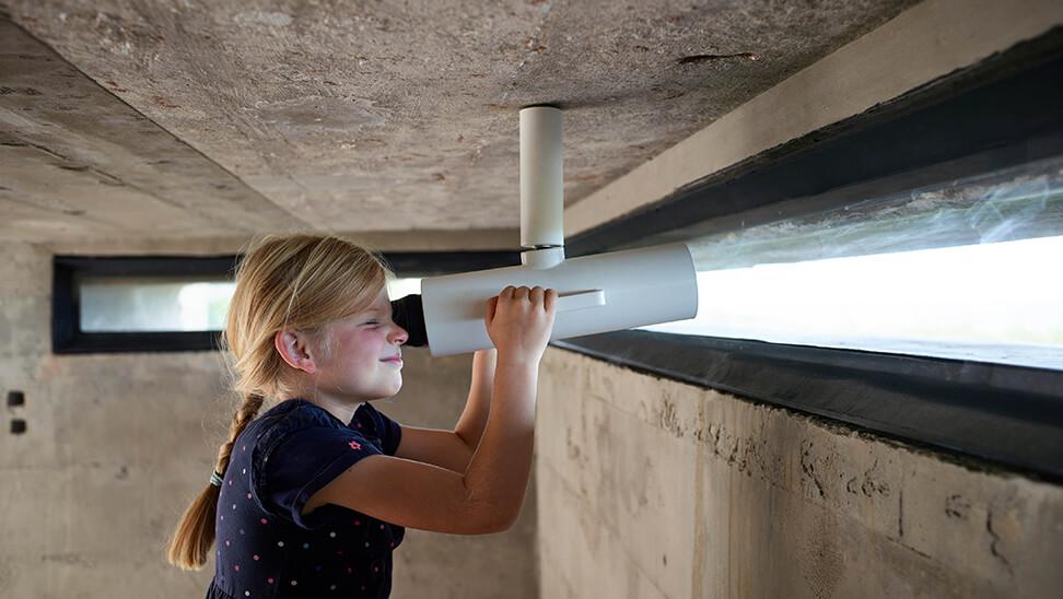 Meisje kijkt door verrekijker in bunker