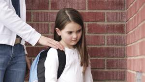 leraar legt hand op de schouder van meisje