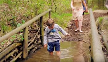 Jongen wandelt door het water (Blotevoetenpad)