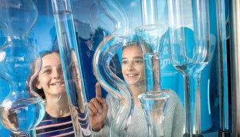 2 meisjes kijken enthousiast naar buizen met water