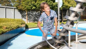 Jongen speelt buiten met waterturbine