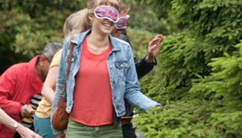 vrouw met blinddoek voelt aan plant