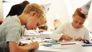 kind tekent aan tafel
