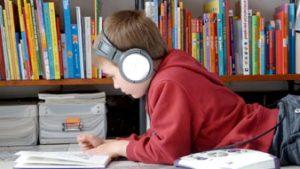Jongen leest boek in Bibliotheek Dilbeek.