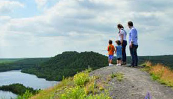 gezin staat op berg met zicht op water