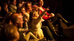 kind in publiek wijst naar voorstelling
