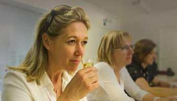 Vrouw proeft aan glaasje met jenever