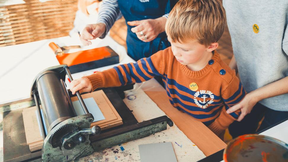 kind met drukpers in Industriemuseum