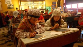 Kinderen volgen les in traditionele kleding - Oud Schoolgebouw Sincfala