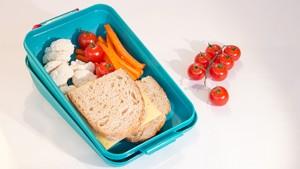 Brooddoos met boterhammen en kleurrijke groenten zoals tomaten, wortelen en bloemkool