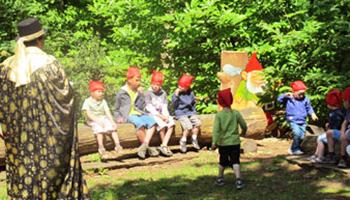 kinderen zitten op boomstam in sprookjesbos