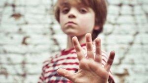 Een jongen steekt zijn hand uit en toont 5 vingers
