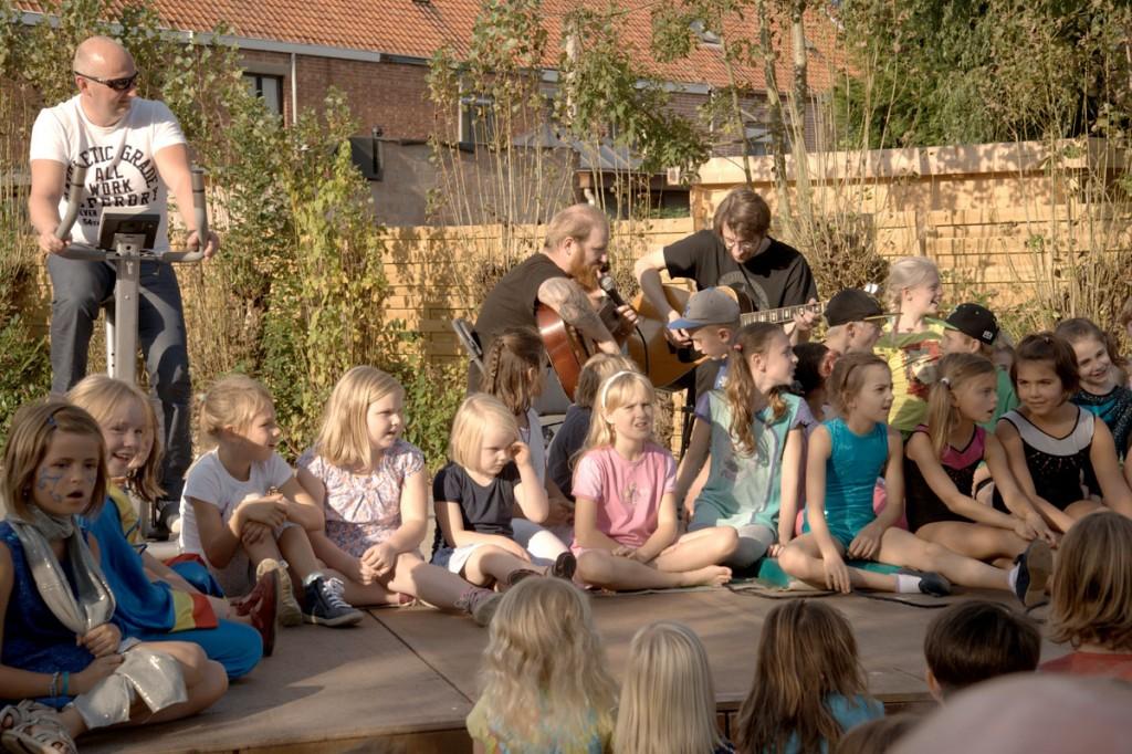 Kinderen zitten in cirkel bij 2 mannen met een gitaar