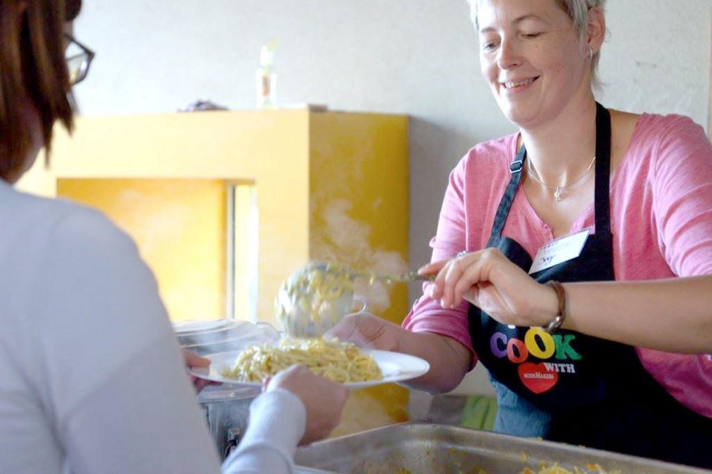 Vrouw schept macaroni met kaassaus