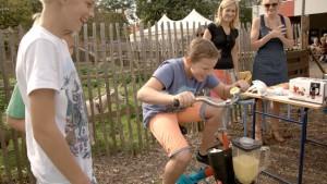 Een kind op een bakfiets trapt om een sapje te mixen terwijl volwassenen en kinderen toekijken