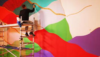 kunstenaar werkt aan muur in Mima