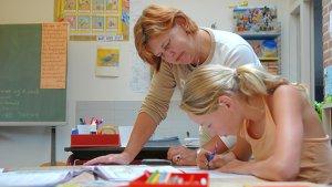leraar helpt leerling in de klas