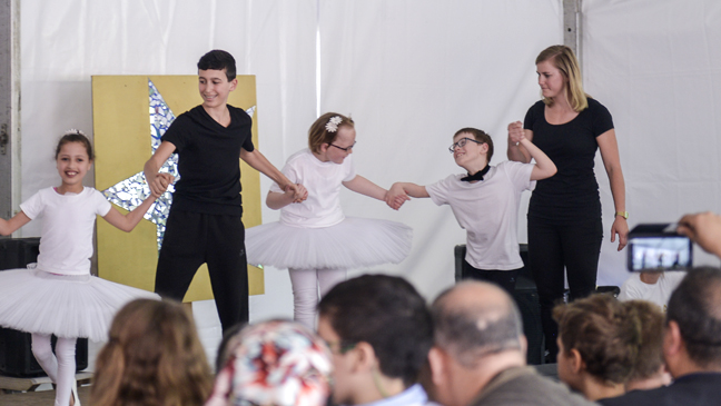 Leraren en leerlingen dansen op een podium tijdens schoolfeest