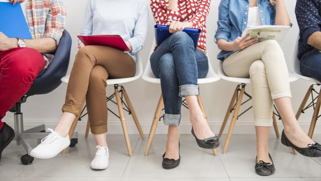 sollicitanten zitten op een rij stoelen te wachten op sollicitatiegesprek