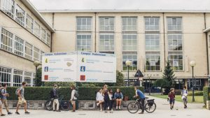 Leerlingen voor het schoolgebouw met fiets en te voet