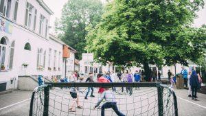 Kinderen voetballen op speelplaats
